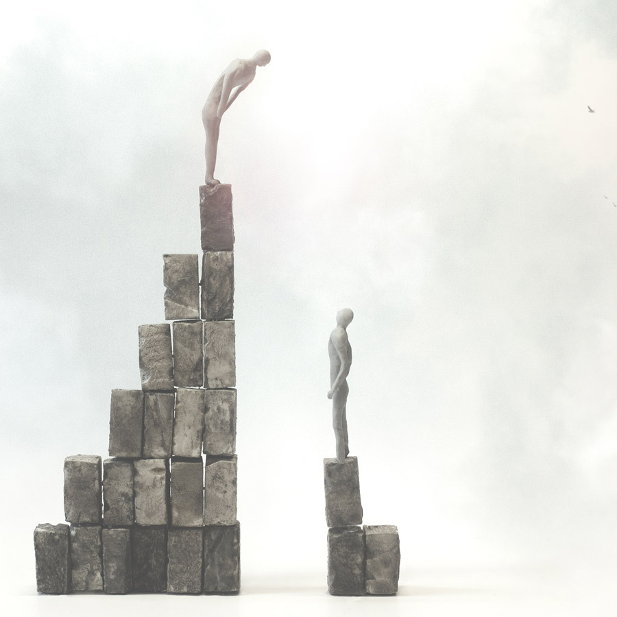 Inequality concept - one person on a taller pile of stones than the other