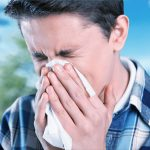 Young man sneezing with tissue over face