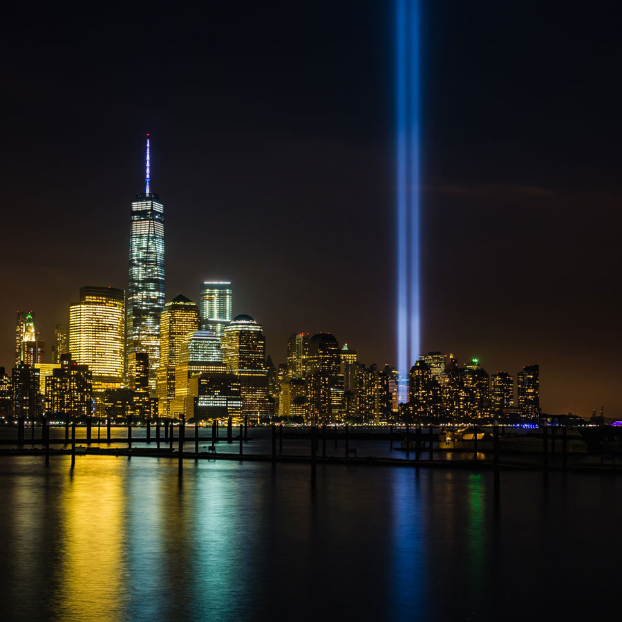 New York skyline at night showing 9/11 memorial lights
